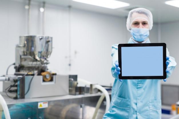 Naukowiec pokazuje pustą tabletkę w pobliżu maszyn
