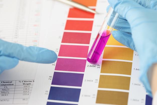 Naukowiec porównuje fioletowy płyn w probówce do laboratorium z kolorowym paskiem do analizy chemicznej