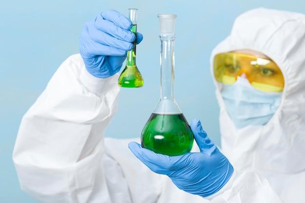 Naukowiec posiadający zielone chemikalia