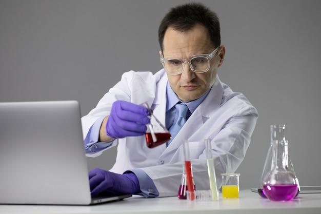 Naukowiec pracujący w laboratorium z kolb próbnych i komputera
