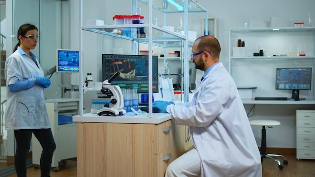 Naukowiec pracujący w nowocześnie wyposażonym laboratorium rozwoju wirusa cheching z mikroskopem. wieloetniczny zespół badający ewolucję szczepionek przy użyciu zaawansowanych technologicznie i chemicznych narzędzi do badań naukowych.