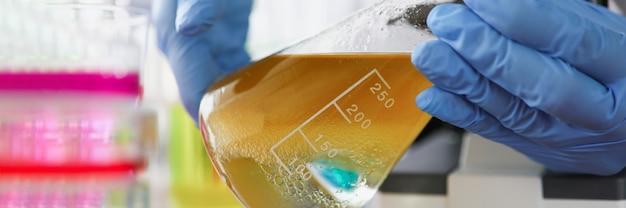 Naukowiec prowadzi badania cieczy w żółtobrązowej kolbie