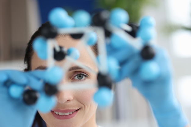 Naukowiec przygląda się modelowi makiety złożonej z cząsteczek, od których zależą właściwości substancji