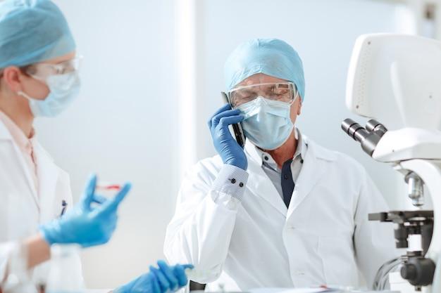 Naukowiec rozmawia przez telefon komórkowy w laboratorium