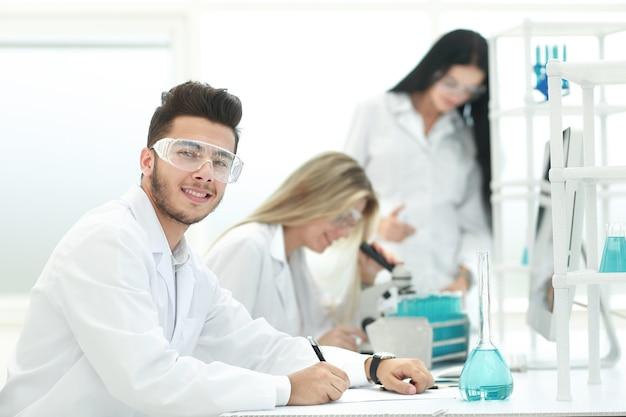 Naukowiec siedzący przy biurku w laboratorium