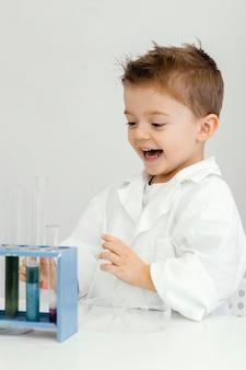 Naukowiec smiley boy w laboratorium z probówkami
