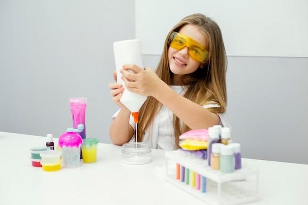 Naukowiec smiley girl dokonywanie szlamu w laboratorium