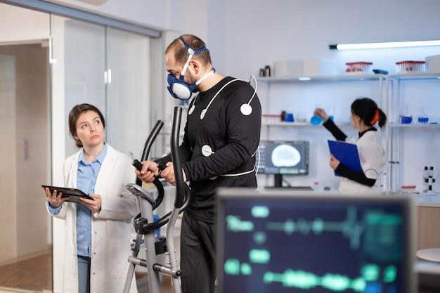 Naukowiec sportu monitorujący wydajność cardio sportowca, tętno, testujący sportowca w treningu crossowym w laboratorium. laboratorium ekg zdrowego ciała.