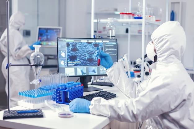 Naukowiec sprawdzający probówkę z analizą krwi ubrany w środki ochrony zdrowia podczas epidemii koronawirusa