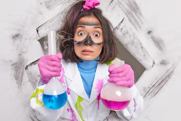 Naukowiec trzyma płynną substancję w kolbach z parą pracuje w naukowym laboratorium chemicznym nosi biały fartuch przedziera się przez papier