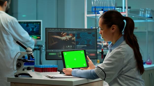 Naukowiec trzyma tablet z zieloną makieta, patrząc na urządzenie z kluczem chroma, na białym tle wyświetlacz. mikrobiolodzy prowadzący badania nad wirusami, w tle badacz z laboratorium ludzkiego pracujący przy opracowywaniu szczepionek.