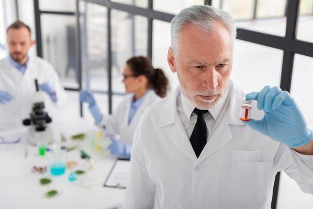Naukowiec trzymając fiolkę średni strzał