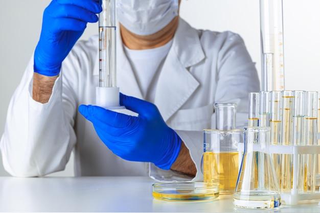 Naukowiec trzymając się za ręce trochę płynu w naczyniu w laboratorium do analizy, z bliska
