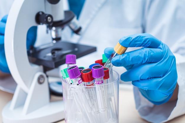 Naukowiec trzymający i analizujący probówkę z próbką mikrobiologiczną pod mikroskopem.