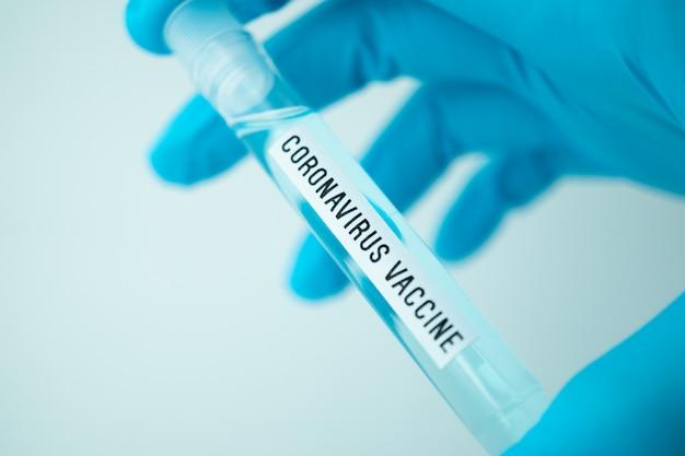 Naukowiec trzymający probówkę z etykietą szczepionki przeciwko covid-19 lub koronawirusowi, testy laboratoryjne w celu wynalezienia leku na pandemię