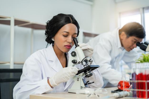 Naukowiec używa mikroskop w laboratorium z próbnej tubki tłem. technologia medycznej opieki zdrowotnej oraz koncepcja badań i rozwoju farmaceutycznego
