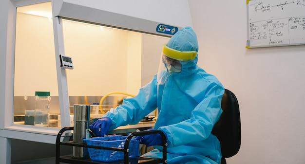 Naukowiec w eksperymencie z jednorodnym pipetowaniem ppe w szafie bezpieczeństwa biologicznego