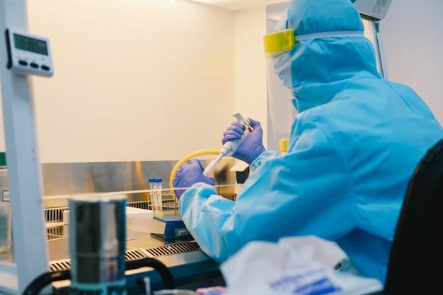 Naukowiec w eksperymencie z próbką pipetowania jednorodnego ppe w gabinecie bezpieczeństwa biologicznego (bsc).