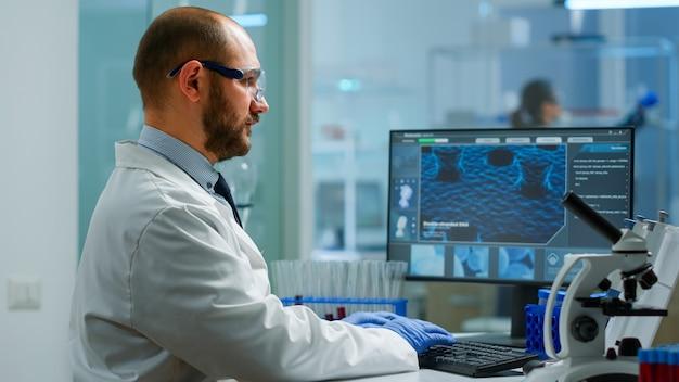 Naukowiec w fartuchu analizującym próbkę krwi z probówki. badacz viorolog w profesjonalnym laboratorium pracującym nad odkrywaniem leczenia medycznego, zespół lekarzy analizujących ewolucję szczepionek