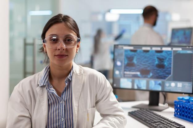 Naukowiec w fartuchu laboratoryjnym siedzący w laboratorium patrzący na uśmiechający się aparat