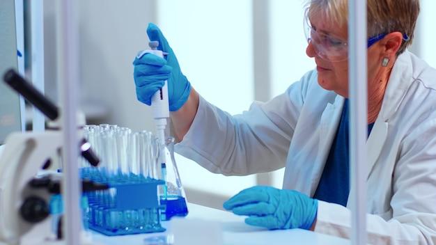 Naukowiec w nowocześnie wyposażonym laboratorium medycznym badający odkrywanie leków za pomocą mikropipety. wieloetniczne osoby badające ewolucję szczepionek przy użyciu zaawansowanych technologii i technologii badających leczenie