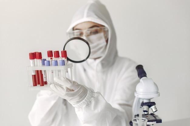 Naukowiec w odzieży kombinezonowej bada próbkę koronawirusa w laboratorium