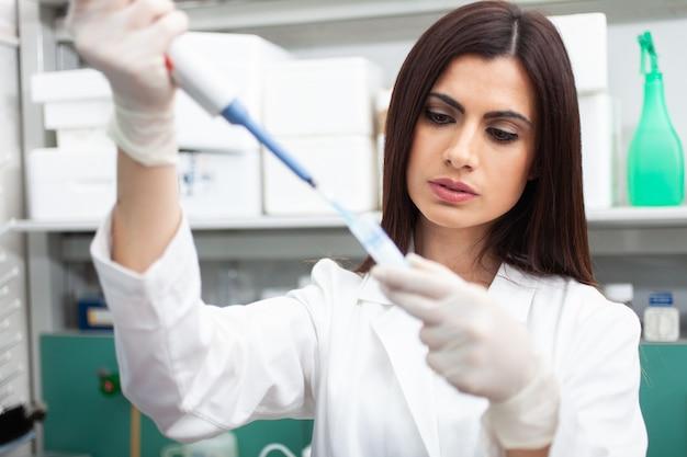 Naukowiec wkłada próbkę do probówki