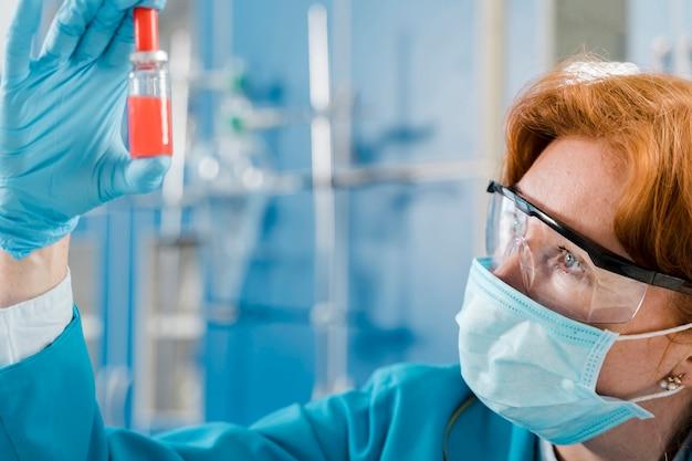 Naukowiec z maską patrzeje próbkę
