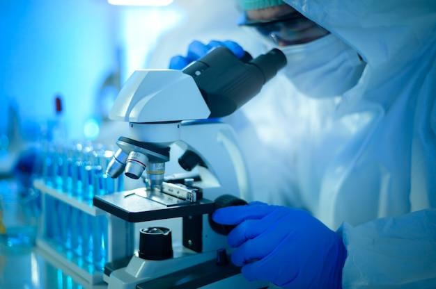 Naukowiec za pomocą mikroskopu podczas eksperymentu w laboratorium, nauki i technologii koncepcji opieki zdrowotnej