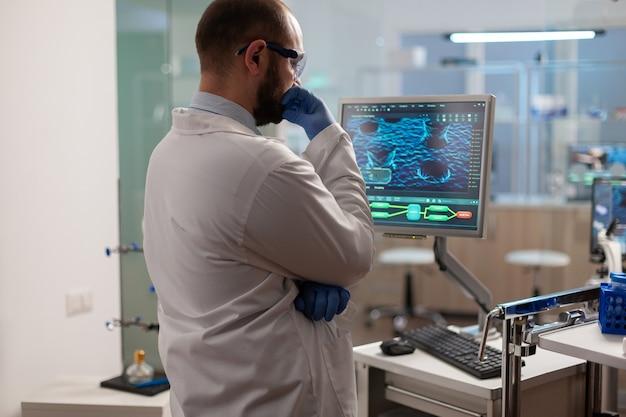 Naukowiec zaniepokojony ewolucją wirusa analizujący obraz skanu dna