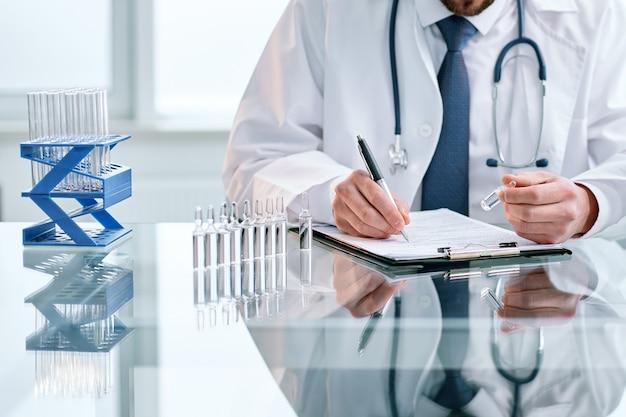 Naukowiec zapisuje wyniki badań w czasopiśmie laboratoryjnym z koncepcją ochrony zdrowia