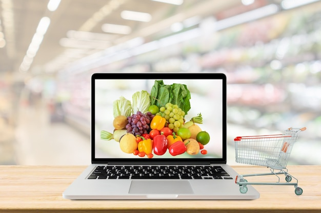 Nawa supermarketu niewyraźne tło z laptopem i koszykiem na drewnianym stole spożywczym online koncepcja