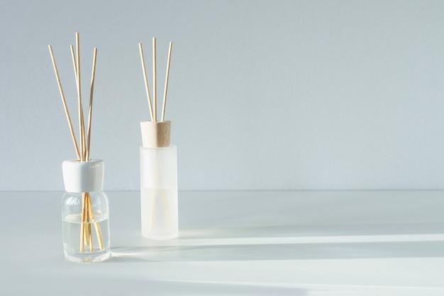Nawiewniki trzcinowe na stole. aromatyczne paluszki o kwiatowym zapachu. mieszkanie komercyjne, widok z przodu. zapach aromaterapeutyczny. skopiuj miejsce