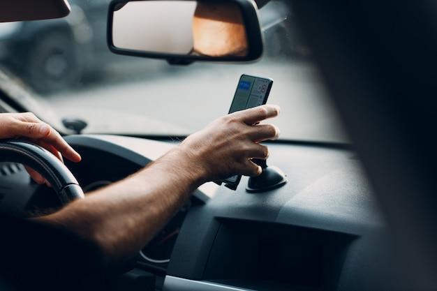 Nawigator w podmiejskim transporcie pojazdów samochodowych. kierowca mężczyzna wskazując ręką palec telefon komórkowy nawigator aplikacji podczas jazdy samochodem.