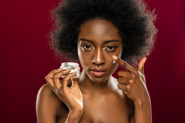Nawilzacz skory. portret pięknej kobiety afro american patrząc na ciebie podczas nakładania kremu na policzek