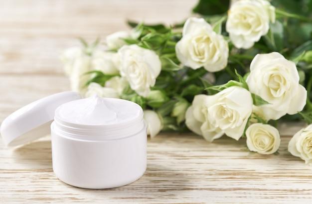 Nawilżający krem do cery wrażliwej, kosmetyk spa i naturalny produkt do pielęgnacji czystej skóry na tle białych róż.