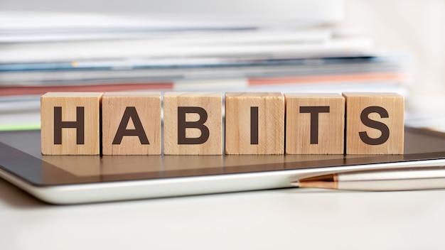 Nawyki słowne wypisane na drewnianych kostkach stojących na tablecie, w tle stos dokumentów, selektywne skupienie. może być używany do koncepcji biznesowej, edukacyjnej, finansowej, marketingowej.