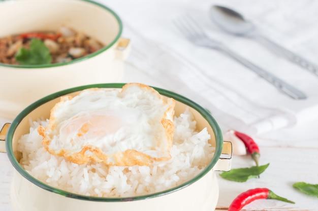 Nazwa tajskiego jedzenia pad ka prao, gotowany ryż i jajko sadzone w klasycznym pojemniku na żywność obok smażonej wieprzowiny z liśćmi bazylii na białym drewnianym stole