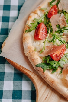 Neapolitańska pizza z szynką, serem, rukolą, bazylią, pomidorami posypanymi serem na drewnianej desce na obrusie w komórce z miejscem na tekst