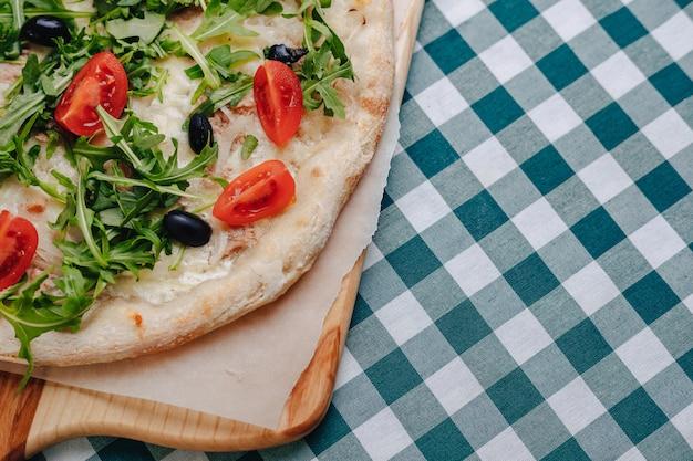 Neapolitańska pizza z tuńczykiem, serem, rukolą, bazylią, pomidorami, oliwkami, posypana serem na drewnianym stole na obrusie w komórce z miejscem na tekst.
