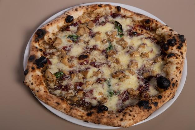 Neapolitańska rzemieślnicza pizza z mozzarellą, kiełbasą, czarną truflą, bazylią, czarnym pieprzem i parmezanem. widok z góry.