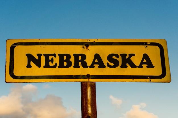 Nebraska stan na starym koloru żółtego znaku z niebieskim niebem