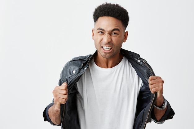 Negatywne emocje. odosobniony portret młody atrakcyjny nieszczęśliwy czarnoskóry męski uczeń z afro fryzurą w przypadkowym stroju drzeje ubrania z rękami, patrzeje w kamerze z gniewnym wyrażeniem.