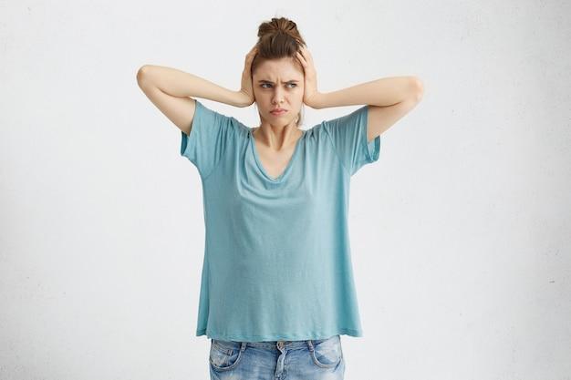Negatywne emocje, reakcje i postawa człowieka. sfrustrowana zirytowana kobieta zakrywająca uszy dłońmi, rozdrażniona głośnym irytującym hałasem