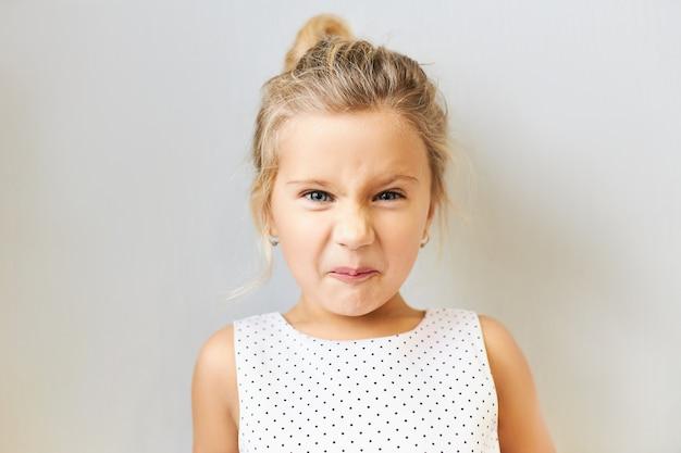 Negatywne ludzkie emocje i reakcje. pojedyncze ujęcie niezadowolonej, zirytowanej małej dziewczynki, wykrzywionej z obrzydzeniem, drażniącej cię, zepsute niegrzeczne dziecko płci żeńskiej pokazujące swój temperament