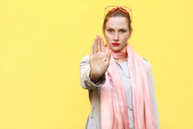 """Negatywne ludzkie emocje, mowa ciała. na białym tle strzał studio. młoda dorosła kobieta o złym nastawieniu, wykonująca gest zatrzymania z dłonią na zewnątrz, mówiąca """"nie"""", wyrażając zaprzeczenie lub ograniczenie. skoncentruj się na rękę."""