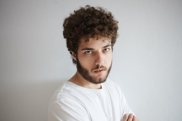 Negatywny wyraz twarzy, uczucia, reakcje i emocje człowieka. zdjęcie w głowę ponurego przystojnego młodego europejczyka z puszystą, gęstą brodą, z niezadowolonym, badawczym spojrzeniem