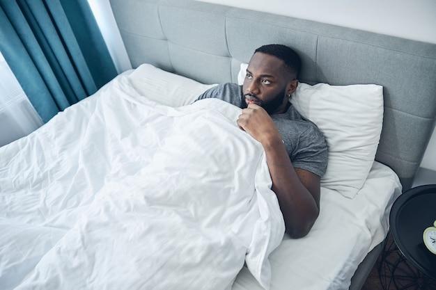 Negatywny zachwycony młody człowiek leżący w łóżku i pogrążony w myślach, marzący o wakacjach