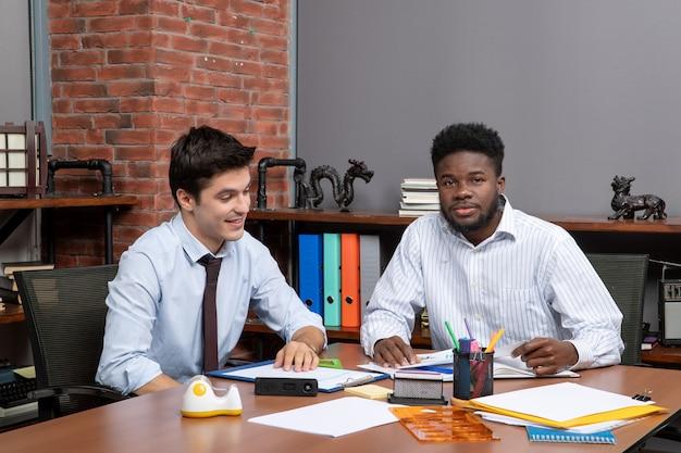 Negocjacje biznesowe z widokiem z przodu dwóch współpracowników pracujących w biurze