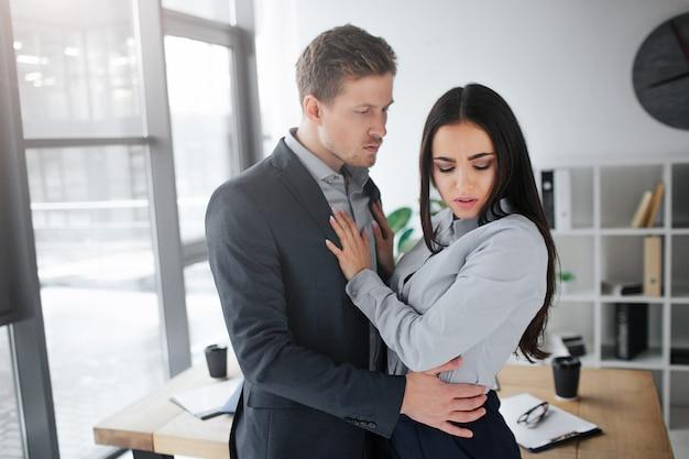 Nękanie pojęciowe. cicha i cicha młoda brunetka patrzy w dół. trzyma dłonie na piersi mężczyzny.